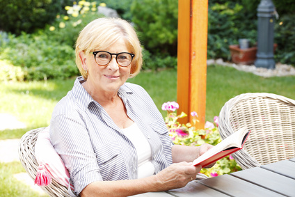 Portrait of a smiling senior woman enjoying a good book for relaxation while sitting at garden at home.